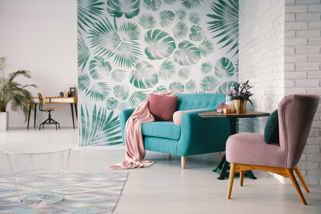 Chair and turquoise sofa in green living room interior with leaves wallpaper and table. Real photo